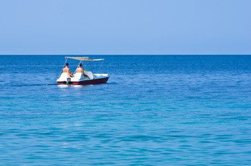 Couple driving a pedal boat on a vacation at Aegean sea