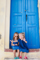 Little adorable girls sitting near old blue door in Greek