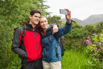 Happy couple on a hike taking a selfie