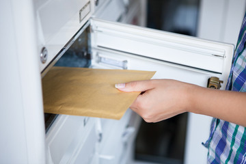 Woman's hand pulling envelop from mailbox