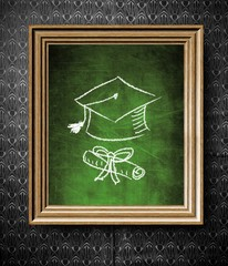 Graduation cap and diploma chalkboard in old wooden frame