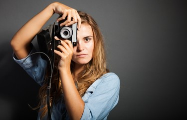 Photographer in jeans jacket taking pictures with old camera