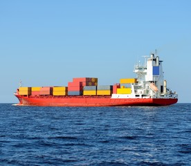red containership loaded with colorful cargo containers at the s
