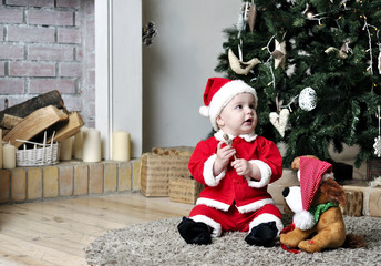 Baby in Santa costume sit near Christmas tree with toy