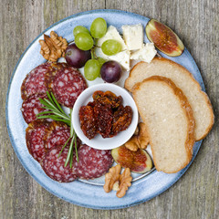 Plate with snacks, sausage, cheese, nuts and fruit