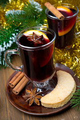 two glasses of mulled wine with spices in glass and cookies