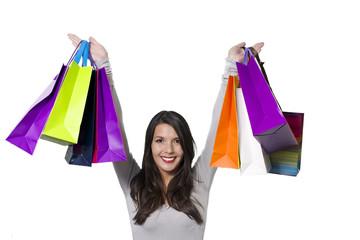 Jubilant woman holding aloft shopping bags