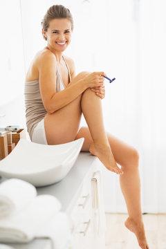 Happy woman shaving legs in bathroom