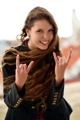 portrait of happy woman doing rock symbol