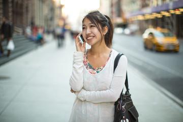 Asian woman walking talking on a cellphone