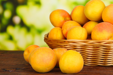 Fresh natural apricot in wicker basket on wooden table