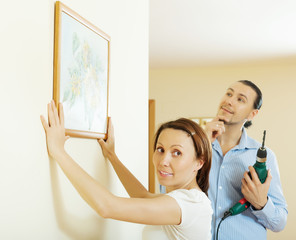 couple choosing point for picture on wall at home