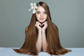 Wall Mural - Portrait of beautiful girl with long hairs with an orchid