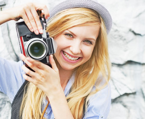 Portrait of smiling hipster girl making photo with retro camera