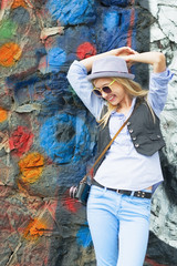 Smiling hipster girl against urban wall