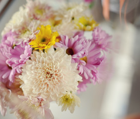 on the windowsill in a wet glass is white vase with a bouquet of