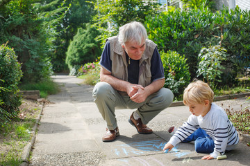 Little blond toddler boy and happy grandfather painting with cha
