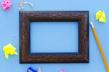 empty picture frame on a blue background with writing equipment