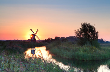 Wall Mural - sunrise with sun behind Dutch windmill