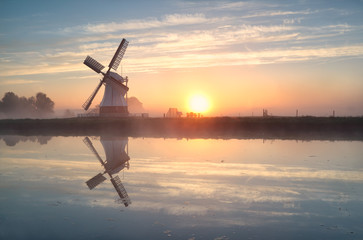 Wall Mural - Dutch windmill reflected in river at sunrise