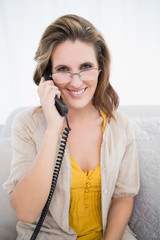Smiling woman with glasses talking on the telephone