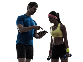 Wall Mural - woman exercising fitness  man coach using digital tablet silhoue