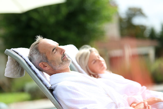 Senior couple in spa hotel relaxing in long chairs