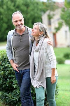 Cheerful mature couple walking in garden