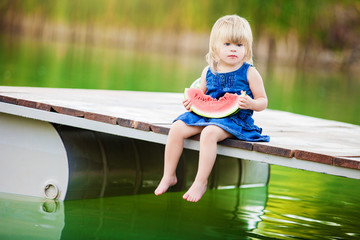Happy smiling child eating watermelon on lake