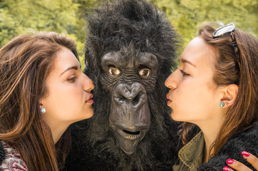 Two Girls kissing a Gorilla