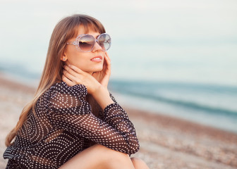 fashion girl sitting on the beach wearing sunglasses