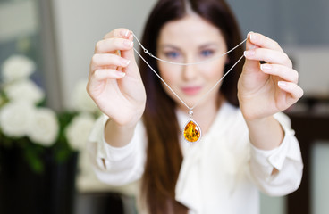 Woman keeping necklace with yellow sapphire at jeweler's shop