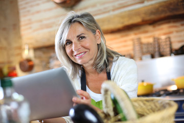 Senior woman cooking with help of recipe on tablet