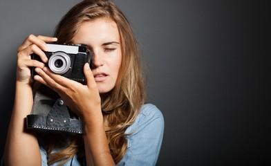 Photographer woman holding old camera, taking pictures