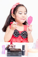 Little Asian child playing with mothers makeup