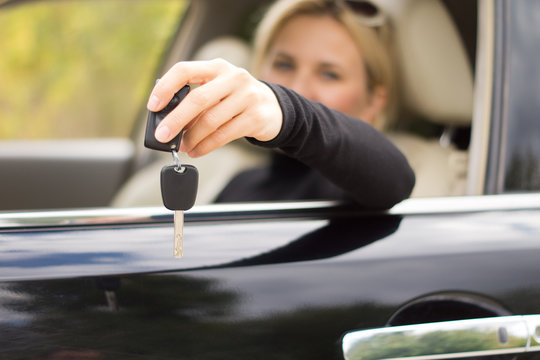 Woman driver holding out her keys