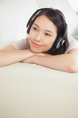 Content asian girl lying on the sofa and listening to music
