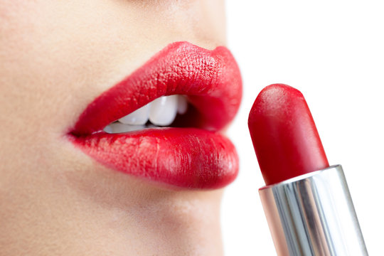 Extreme close up on model applying red lipstick