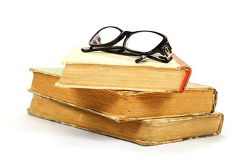 Stack of old books and glasses on a white background.