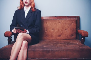 Businesswoman sitting on sofa reading on tablet