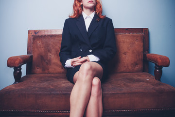 Confident young businesswoman sitting on sofa