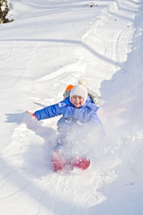 Little girl on a sled in the winter
