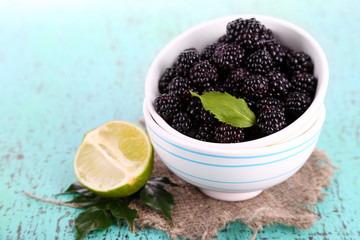 Blackberries in small bowl on sackcloth  on wooden background