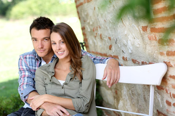 Lovers relaxing on bench in countryside