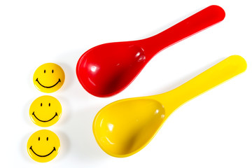 Red with yellow plastic spoon isolated on white background