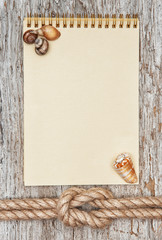 Ship rope, shells, notebook and wood background