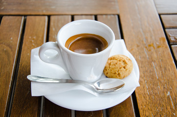 White espresso cup with biscuit standing on the wooden table