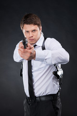 Bodyguard. Confident young man in shirt and tie holding gun and