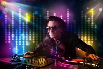 Dj playing songs in a disco with light show