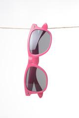 Gafas de sol colgadas de una cuerda de color rosa